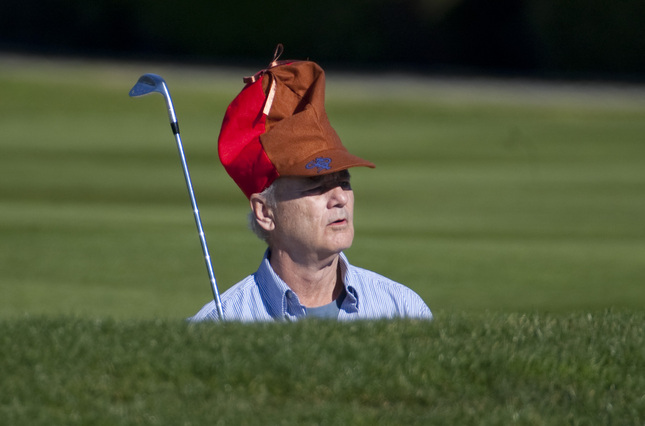 Comedian Bill Murray wears an 'Elmer Fudd' hat while waiting to hit out of a fairway bunker on the 16th hole during Round 3 of the AT&T Pebble Beach National Pro-Am at Pebble Beach Golf Links in Pebble Beach Saturday Feb. 12, 2011. (Photo by Patrick Tehan/Mercury News)